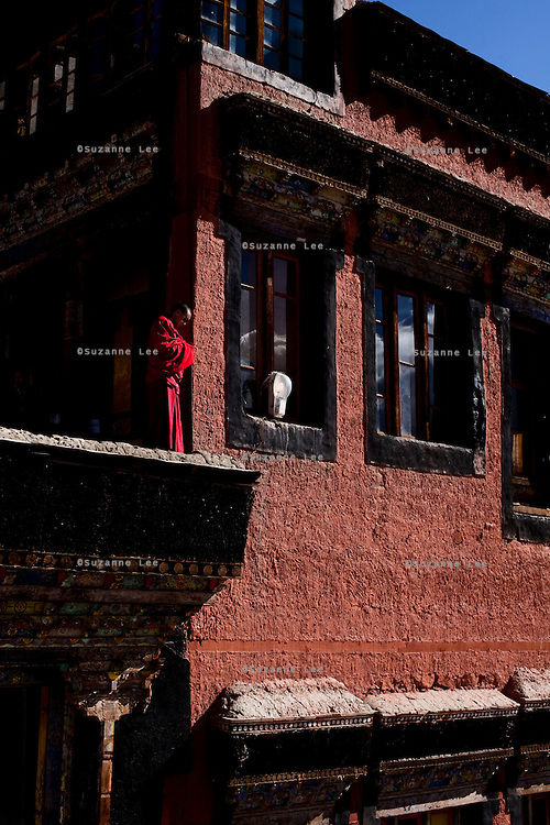 A monk stands on a wall in Thiksey Gompa, Leh, Ladakh..*Pre-season Jeep road trip from Delhi to Amritsar, Srinagar, Kargil, Lamayuru, Leh, Khardung La, Tso Moriri and back to Delhi in May 2010. Photo by Suzanne Lee