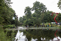 Denham, UK. 24 July, 2020. Environmental activists from HS2 Rebellion, including Larch (l) and Swan (r) on a line above the shallow river Colne, try to protect an ancient alder tree from destruction in connection with works for the HS2 high-speed rail link in Denham Country Park. A large policing operation involving the Metropolitan Police, Thames Valley Police, City of London Police and Hampshire Police as well as the National Eviction Team was put in place to enable HS2 to remove the tree.