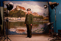 1985, Lhasa, Tibetan Autonomous Region, China --- A Chinese officer in Lhasa poses in front of a tableaux depicting Potala Palace for a studio photograph. --- Image by © Owen Franken/CORBIS