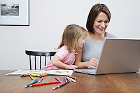 Mother sitting at table with daughter (3-4) using laptop smiling