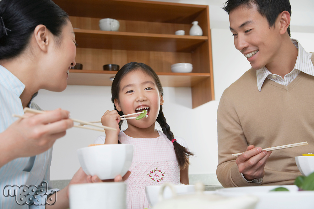 Young couple and daughter eating a meal with chopsticks