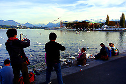 Tourists visit the Lucerne shore of beautiful Lake Lucerne.