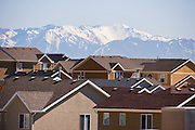A tightly-packed community housing development with snow-covered mountains in the distance.