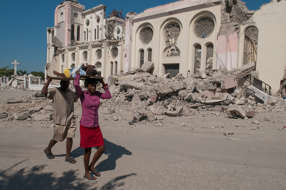 1/15/10 12:28:44 PM -- Port-Au-Prince, Haiti. -- Daily coverage of the aftermath of the 7.0 earthquake in Haiti -- Paul Wendy, 8 years old and injured in Tuesday's earthquake, is carried by his mother Lamesa Jean and father Fritz Paul past the wreckage of Haiti's National Cathedral, in Port au Prince, Haiti Friday Jan. 15, 2010. (Photo by William B. Plowman ©)