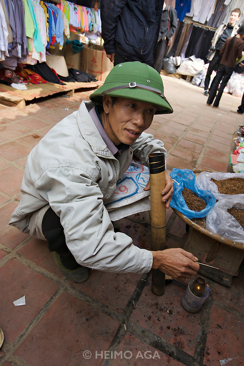 Tam Duong market. Man with bamboo pipe.
