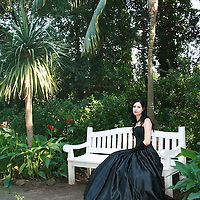 Young woman wearing regency dress, sitting on a bench in a botanic garden