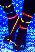 Glowing coils and rings on a pair of dark legs and feet.Black light