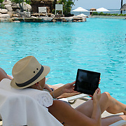 Woman with an iPad by the pool. Marriott CasaMagna Puerto Vallarta. Jalisco, Mexico.