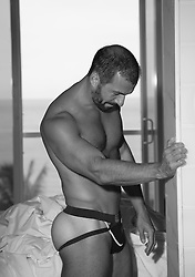 Latin man in a jock strap at home