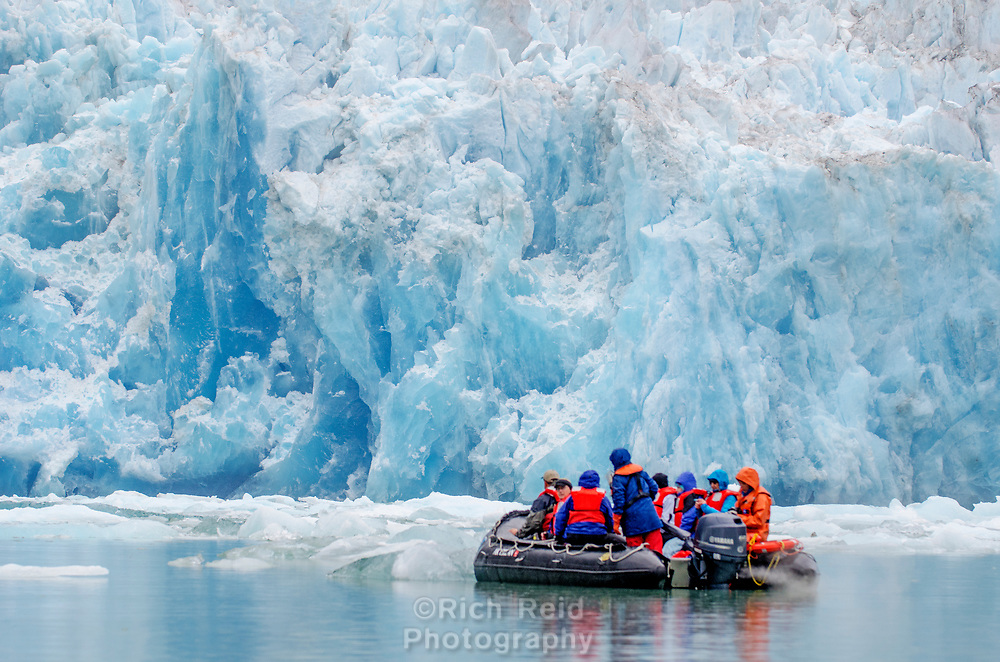 Expedition craft dwarfed by South Sawyer Glacier in Tracy Arm - Ford Terror Wilderness, Alaska.