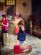 25 AUGUST 2018 - GEORGE TOWN, PENANG, MALAYSIA: A woman prays in Yap Kongsi Temple on Ghost Day, the full moon day (or night) that falls in the middle of Hungry Ghost month. The Ghost Festival, also known as the Hungry Ghost Festival is a traditional Taoist and Buddhist festival held in Chinese communities throughout Asia. Ghost Day, is on the 15th night of the seventh month (25 August in 2018). During Ghost Festival, the deceased are believed to visit the living. In many Chinese communities, there are Chinese operas and puppet shows and elaborate banquets are staged to appease the ghosts.      PHOTO BY JACK KURTZ