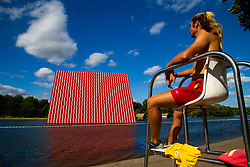 Lifeguard Gabriel Iowan, 29, at the Serpentine's lido gazes across the water at artist Christo's 20m high installation on The Serpentine made from over 7000 barrels, titled The Mastaba, which will be on the Serpentine until 23 September 2018. The Installation is comprised of 7,506 horizontally stacked barrels. It is 20m high, 30m wide and 40m long. Hyde Park, London, June 18 2018.