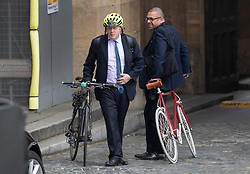 FILE PICTURE © Licensed to London News Pictures. 29/04/2019. London, UK. Boris Johnson (L) walks with his bicycle in Parliament as Conservative Party Deputy Chairman James Cleverly looks on. Photo credit: Peter Macdiarmid/LNP
