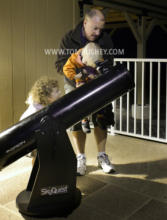 New Paltz, New York - A man picks up a boy so he can look at the moon through a Dobsonian telescope during International Observe the Moon Night at Smolen Observatory at SUNY New Paltz  on Sept. 18, 2010. ©Tom Bushey / The Image Works