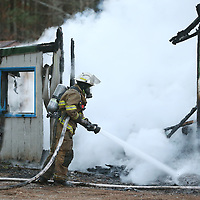 Lauren Wood | Buy at photos.djournal.com<br /> A firefighter with the Palmetto Fire Department sprays down an abandoned home that caught fire Tuesday evening on County Road 900.