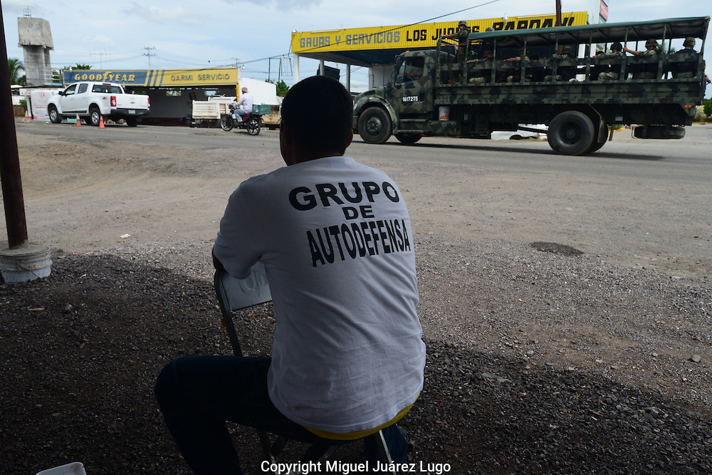 A member of a self--defense force in Tepalcatepec watches an army truck pass by. The local militias have an uneasy relationship with the Mexican army, which deployed in May.
