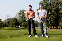 Portrait of young men standing with golf sticks on golf course