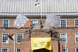 """© Licensed to London News Pictures;25/06/2020; Bristol, UK. Five Extinction Rebellion activists have climbed up the central dome of Bristol City Hall early this morning and say they will stay up there until Bristol City Council commits to ensuring legally clean air in every suburb of the city by April 2021. Extinction Rebellion's Five a Week campaign for clean air is highlighting the number of premature deaths in Bristol due to air pollution. They have set up 296 pairs of shoes on College Green in front of City Hall with the message """"296 Deaths a Year"""" which the campaigners say is the number of people who die each year due to air pollution in the city. Extinction Rebellion demand urgent action from Bristol City Council & WECA (West of England Combined Authority) to protect people's lungs and protect the planet, saying health is intrinsically linked to the health of the environment. XR want Clean Air Equality for Life, not just for the coronavirus Covid-19 lockdown, saying there is a unique opportunity as we come out of lockdown to envision a Bristol that puts people's health and the health of the planet first, and put pressure on elected officials to help build the city back better. Photo credit: Simon Chapman/LNP."""