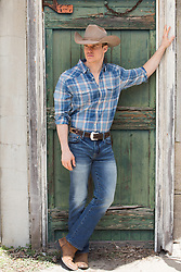 cowboy leaning by a rustic door