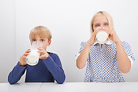 Portrait of children drinking milk at table