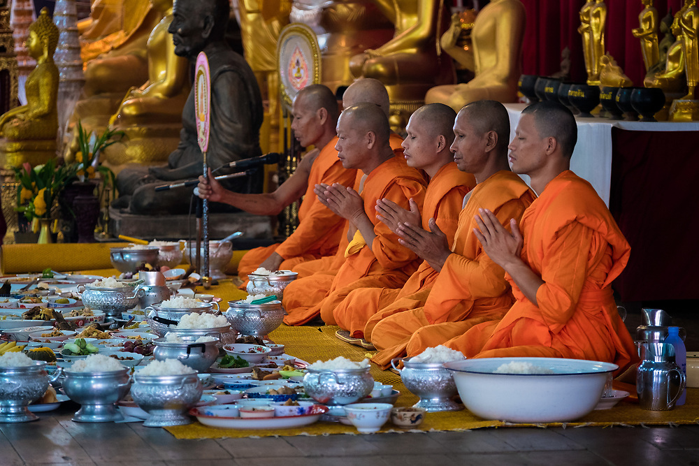 Breakfast is presented to monks at the local temple as a way of giving alms to make merit. The monks will bless the food and will eat first, then the meal will become potluck for the congregation to enjoy. PHOTO BY LEE CRAKER