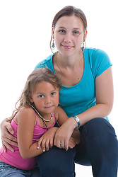 Portrait of a little girl hugging her mother in the studio,