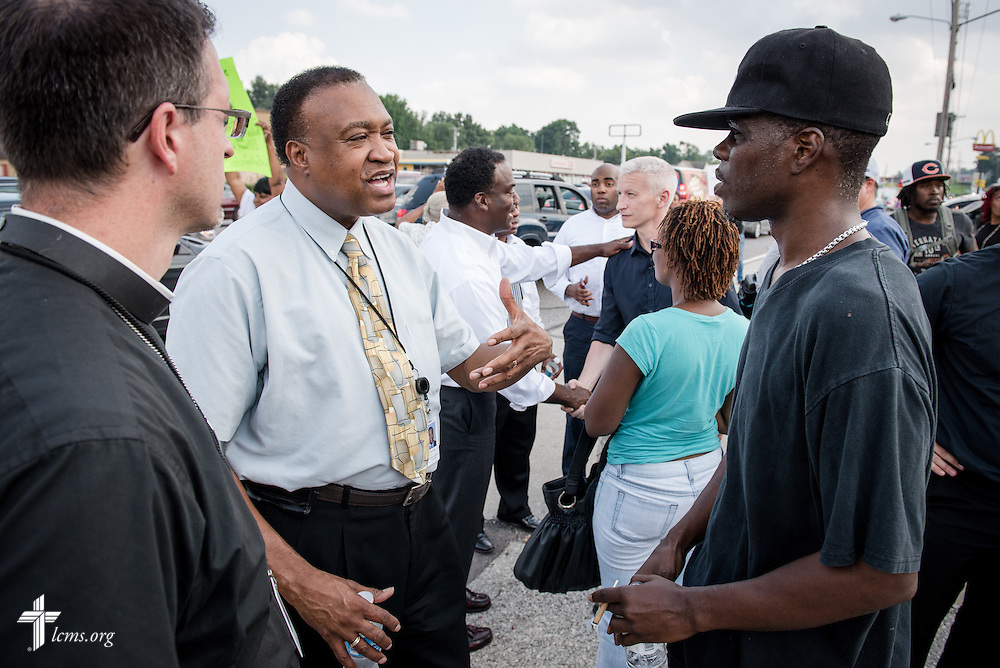 The Rev. Roosevelt Gray, director of LCMS Black Ministry (with tie), and the Rev. Steve Schave, director of LCMS Urban and Inner City Mission (far left) talk to members of the community along West Florissant Avenue on Monday, August 18, 2014, in Ferguson, Mo. LCMS Communications/Erik M. Lunsford
