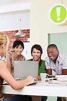 Four people having meeting around laptop laughing.