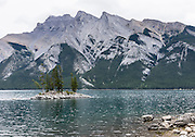 A small island with trees punctuates Lake Minnewanka, Banff National Park, Canadian Rocky Mountains, Alberta, Canada.