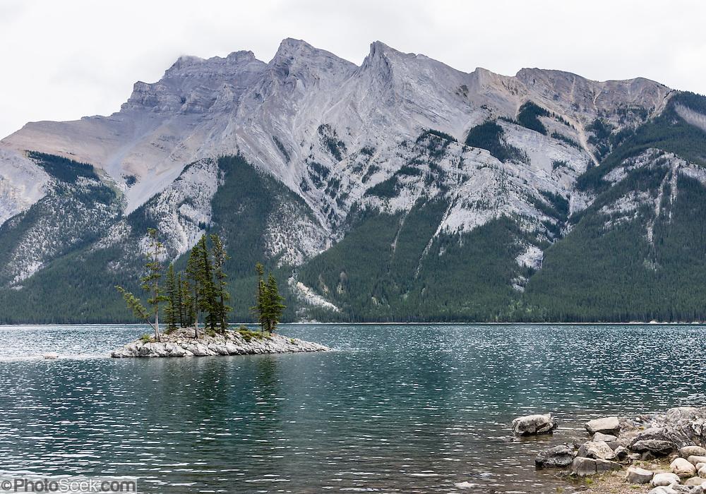 A small island with trees punctuates Lake Minnewanka, Banff National Park, Canadian Rocky Mountains, Alberta, Canada.