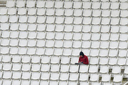 A cold looking spectator on his own in a section of the stands during the first day of the Specsavers County Champ Div 1 match between Hampshire County Cricket Club and Essex County Cricket Club at the Ageas Bowl, Southampton, United Kingdom on 5 April 2019.