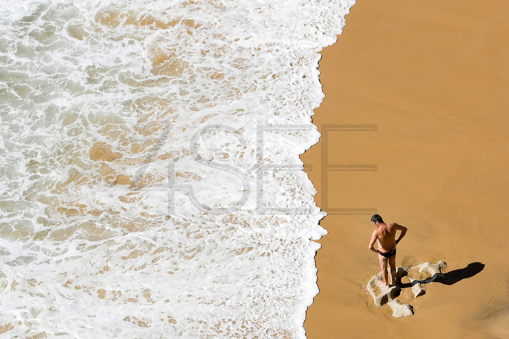 Portuguese Summer. Man watches the waves at Azenhas do Mar beach in Sintra.