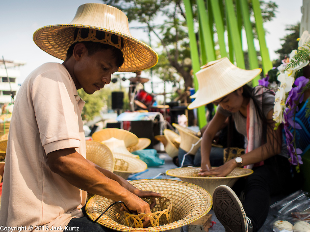 12 FEBRUARY 2015 - BANGKOK, THAILAND: Students make traditional style Thai straw hats at the new floating market opened in Khlong Phadung Krung Kasem, a 5.5 kilometre long canal dug as a moat around Bangkok in the 1850s. The floating market opened at the north end of the canal near Government House, which is the office of the Prime Minister. The floating market was the idea of Thai Prime Minister General Prayuth Chan-ocha. The market will be open until March 1.    PHOTO BY JACK KURTZ