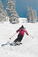 Teenage Girl (16-17) skiing down slope front view.
