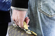 male hand holding a small Louis Vuitton bag