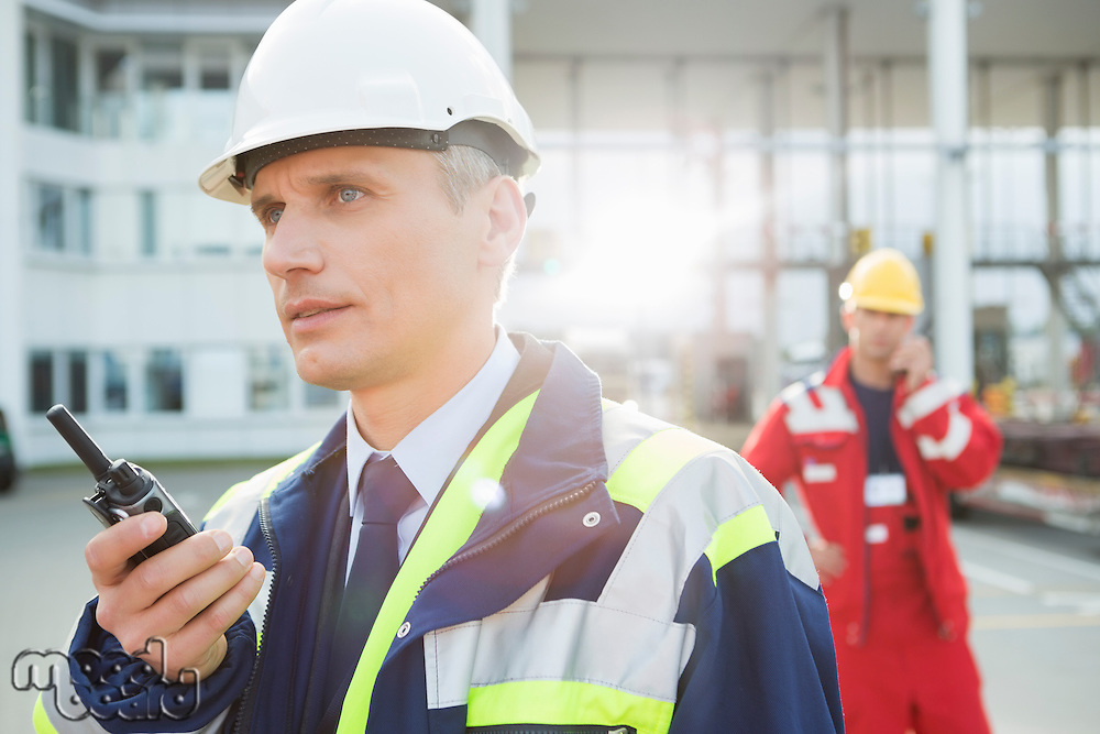 Male worker using walkie-talkie with colleague in background at shipping yard