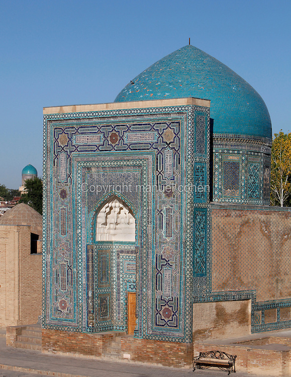 """General view of Mausoleum of the middle group, (""""Nameless 1"""" Mausoleum), 1380s, Shah-I Zindah ensemble, and in the distance the blue cupola of the Bibi-Khanym Madrasah and mausoleum, Samarkand, Uzbekistan, pictured on July 19, 2010, at dawn. The Shah-i-Zinda Complex is a necropolis of mausoleums whose legendary origin dates back to 676 when Kussam-ibn-Abbas arrived to convert the locals to Islam. So successful was he that he was assassinated whilst at prayer. His grave remains the centre of the sacred site which grew over many centuries, especially the 14th and 15th, into an architecturally stunning  exampleof ceramic art. The Mausoleum of the middle group.(""""Nameless 1"""" Mausoleum) was created by Usto Alim Nesefi, and is decorated with relief painted majolica. The portal decorations are notable for the symbol of """"octagonal stars"""". Samarkand, a city on the Silk Road, founded as Afrosiab in the 7th century BC, is a meeting point for the world's cultures. Its most important development was in the Timurid period, 14th to 15th centuries. Picture by Manuel Cohen."""