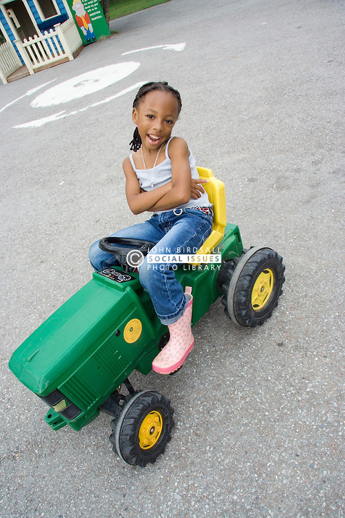 Young girl sitting on a toy tractor,