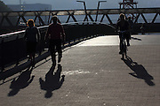 People walk and cycle along the Muelle de Evaristo Churruca walkway along the Nervión river in Bilbao, on a sunny Sunday afternoon in October.