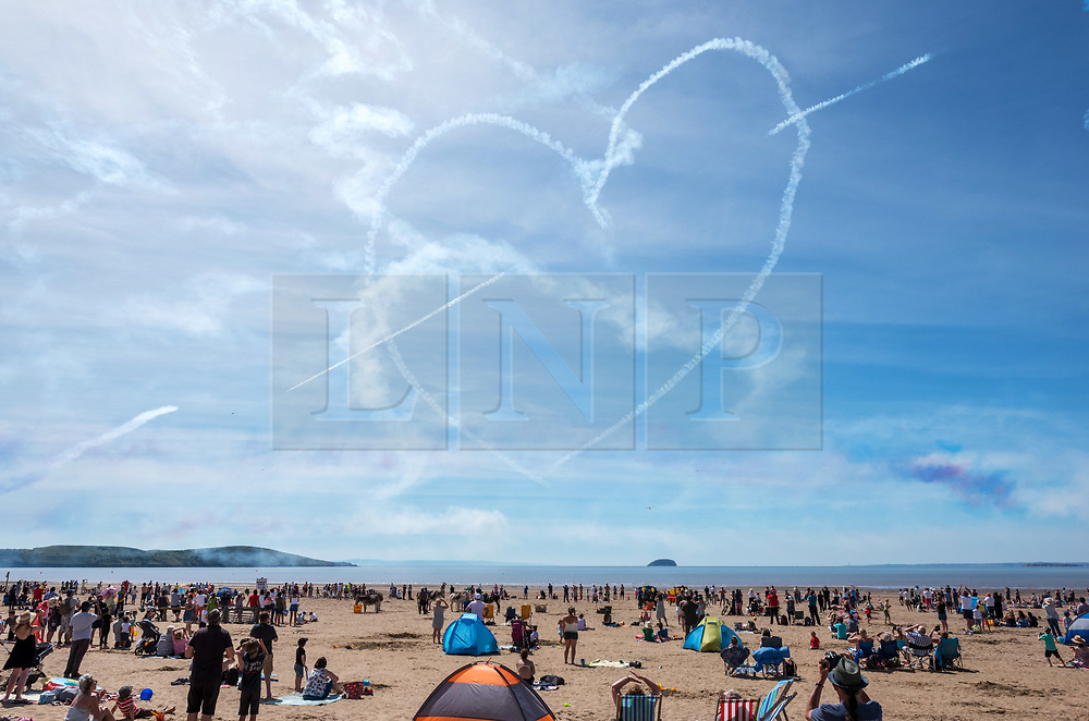 © Licensed to London News Pictures.  24/06/2018; Weston-super-Mare, North Somerset, UK. The RED ARROWS at Weston Air Festival. The Red Arrows draw a heart with an arrow through it with smoke in the sky. Air displays take place over the Seafront and Beach Lawns at Weston-super-Mare, including the Battle of Britain Memorial Flight and the Red Arrows display team. Photo credit: Simon Chapman/LNP