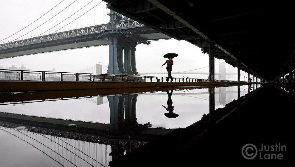 A woman with an umbrella walks along the East River with the Manhattan and Brooklyn Bridges in the background Wednesday 12 October 2005 in New York.