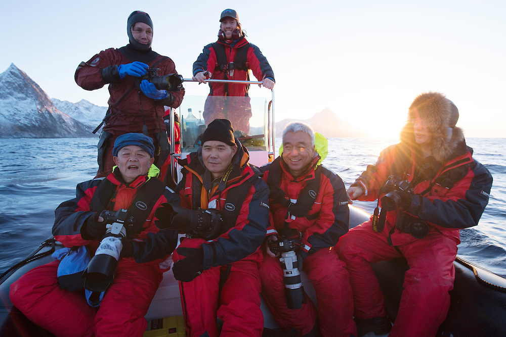 Whale watching and photography visitors/ecotourists from China together with photographer Magnus Lundgren and guide Henrik Jørgensen oin a Zoidiac inflatable rubber boat, outside Senja, Troms county, Norway, Scandinavia
