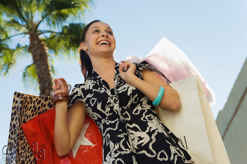 Young woman carrying shopping bags outdoors