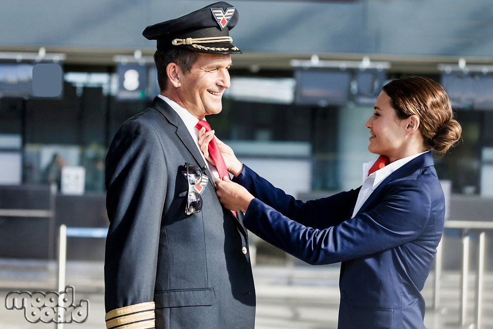 Young attractive flight attendant adjusting pilot neck tie in airport