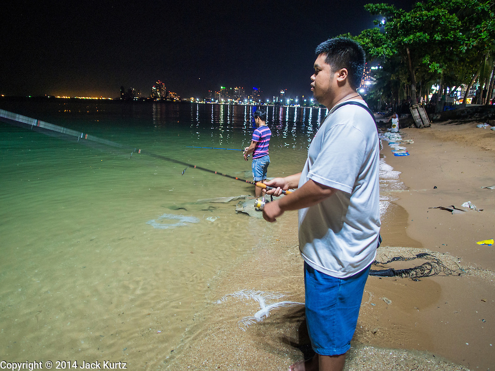 """26 SEPTEMBER 2014 - PATTAYA, CHONBURI, THAILAND: Thais fish in the moonlight on Pataya Beach. Pataya, a beach resort about two hours from Bangkok, has wrestled with a reputation of having a high crime rate and being a haven for sex tourism. After the coup in May, the military government cracked down on other Thai beach resorts, notably Phuket and Hua Hin, putting military officers in charge of law enforcement and cleaning up unlicensed businesses that encroached on beaches. Pattaya city officials have launched their own crackdown and clean up in order to prevent a military crackdown. City officials have vowed to remake Pattaya as a """"family friendly"""" destination. City police and tourist police now patrol """"Walking Street,"""" Pattaya's notorious red light district, and officials are cracking down on unlicensed businesses on the beach.     PHOTO BY JACK KURTZ"""