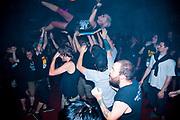 Female Punk rocker crowd surfing at gig, audience at Municipal Waste gig, at Louvre. Prague, Czech Republic. 21 & 22/05/07