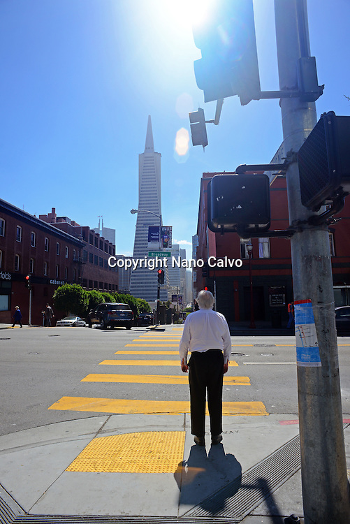 Man waiting to cross street, with Financial District in view. San Francisco.