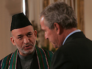 President George W. Bush and President Hamed Karzai Afghanistan answer questions at joint statements and press conference in the East Room of the White House on September 26, 2006.  Photograph:Dennis Brack