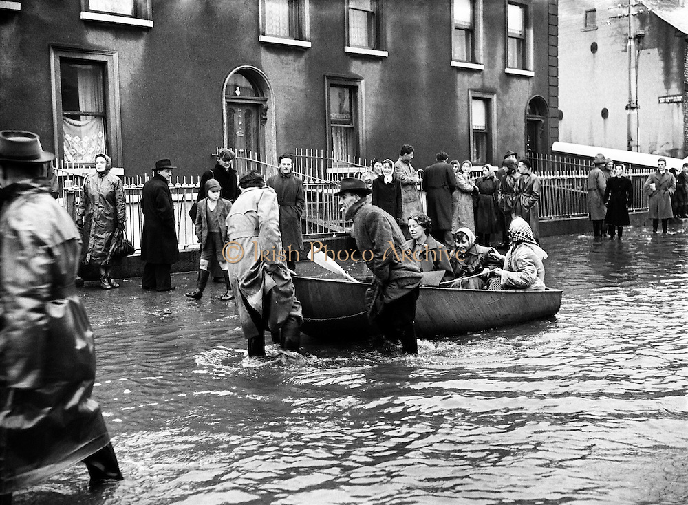 "Flooding at the North Strand, Dublin.8-12/12/1954..From The Irish Times - December 12 2005..SEVERE storms during this week in 1954 brought some of the worst flooding ever seen on the streets of Dublin. Many areas of the city suffered. The north inner city was particularly badly hit..December 7 and 8, 1954, were described in the Irish Press as ""the worst day following the worst night in memory"". Not surprising, since this was one of the worst storms to hit Dublin in the 20th century...On the night of December 7, Ireland was battered by gale-force winds, blizzards, heavy rain and sleet, bringing much of the country to a standstill. Dublin's road and rail network were closed, and air traffic at Dublin airport was grounded by 60mph winds...VENICE..The North Strand was under so much water that the Dublin Evening Mail described it as being ""more like Venice than Dublin"". The Strand Cinema was flooded, and the nearby Cusack's Bar was under six feet of water...One local resident - 70-year-old Mrs Bridget O'Brien, who lived at 5 St Brigid's Cottages off the North Strand Road - was trapped in her home by the rising waters and died...The most serious incident in the area occurred at East Wall Road where the GNR metal railway bridge collapsed and fell into the Tolka. Army engineers dynamited the mouth of the river in a bid to clear it of debris from the fallen railway bridge...Hundreds of evacuees were given temporary accommodation in a shelter run by the Saint John's Ambulance at North Strand. Others rendered homeless by the floods were given food and shelter at the Sisters of Charity convent in North William Street...Author Benedict Kiely was a first-hand witness to the devastation caused by the floods at Drumcondra and he described the water rushing past Lemon's sweet factory on the Tolka as an ""Andean Flood""...Cottage-dwellers living beside the river erected a statue of the Madonna in front of their flooded houses and christened her Our Lady of the Floods...One Fairview wom"