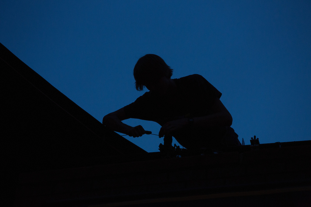 A technician is silhouted against the night sky as he fastens a guy to the edge of the scrim to be used by the Tiger Lillies.